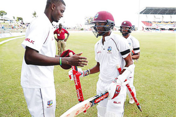 Image of Jason Holder and John Campbell celebrate winning the test