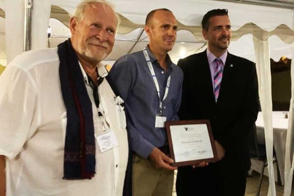 Image of Cdr. Bud Slabbaert, Sapphire Pegasus winner Billy Bohlke and Stuart Johnson, Minister of Tourism, Economic Affairs, Transport and Telecommunication of St Maarten.