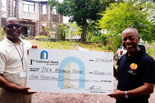 Image of 1st National Bank's Executive Manager for Marketing and PR Robert Fevrier (left) presenting the cheque to FRC Founder Msgr. Patrick Anthony.