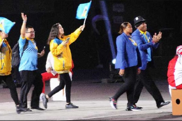"Image: Chef de Mission, David ""Shakes"" Christopher (extreme right), and Assistant to the Chef de Mission, Velica Augustin (beside him), followed by volunteers due to the absence of Saint Lucian coaches and athletes excluding Flag Bearer Luc Chevrier during Friday's March Pass at Friday's Opening Ceremony. (PHOTO: David R Pascal)"
