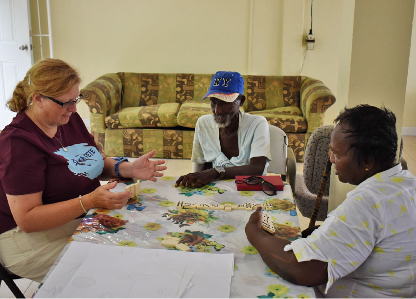 Image: Charlotte Mathurin playing dominos with residents.