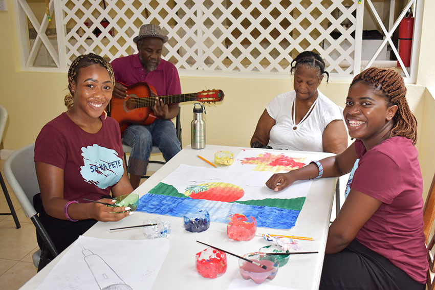 Image: Students Shakerah Brown (far left) and Sarah Russell (far right) painting and singing with Cornerstone residents.