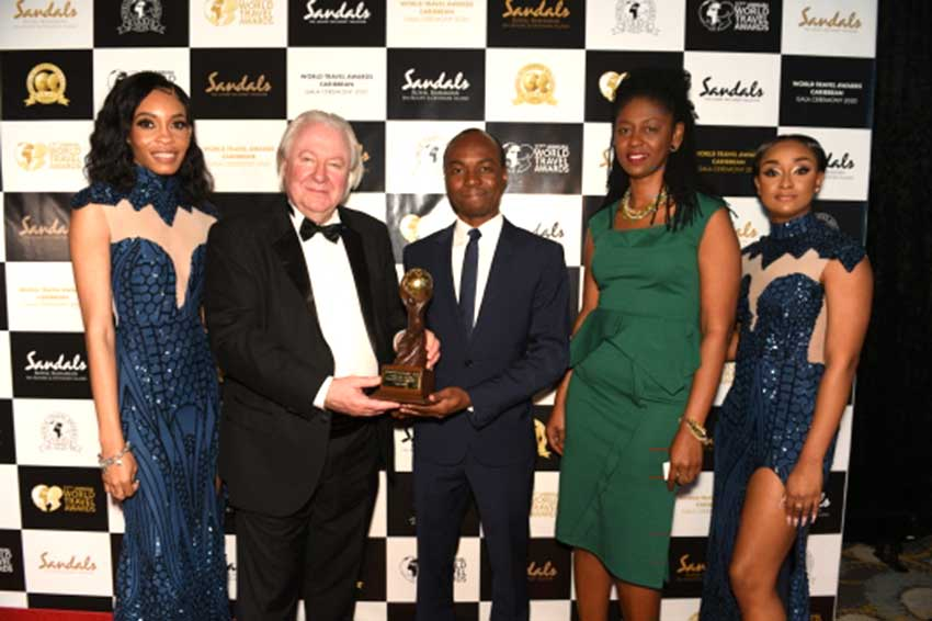image: Tourism Minister Dominic Fedee (center) shows off the prestigious award.