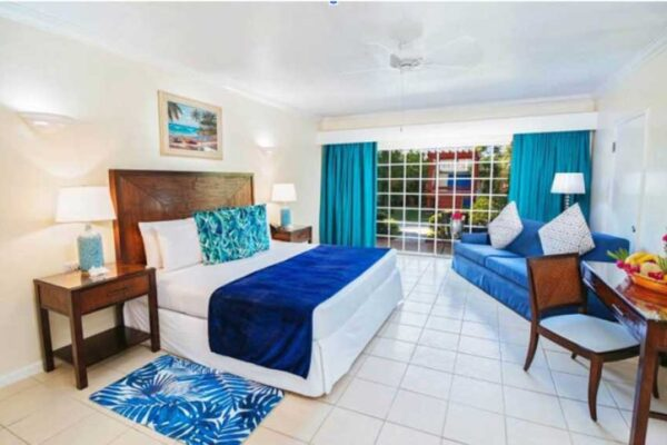 Image: A newly renovated Junior Executive Suite with King bed with Caribbean blue accents.