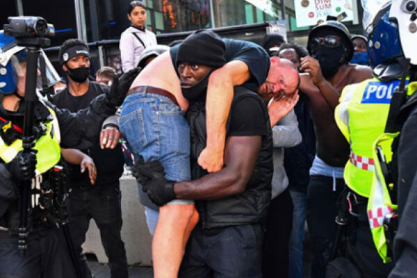 Image of protestor Patrick Hutchinson (centre) carries off an injured white man on his shoulder during a violent scuffle at a protest in London against the murder of George Floyd. Photo Credit: Dylan Martinez/Reuters.