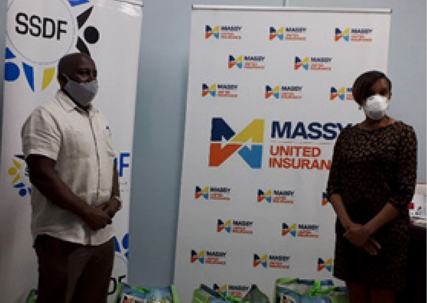Image of SSDF Executive Director Allison Mathurin receiving hampers from Faye Miller, MUI.