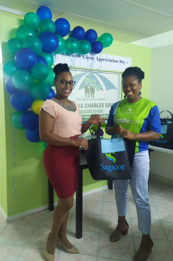 Image: Minerva Charles-David, Advisor with Sagicor presents a back to school package to Ms. Anetta Henry, a client.