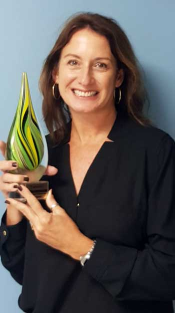 """Image: Heidi Clarke, Executive Director, Sandals Foundation, poses with Agents' Choice Award for """"Favourite Responsible/Philanthropic Travel Foundation"""". The announcement was made at the highly-anticipated Canadian travel industry virtual Gala held on October 1, 2020."""