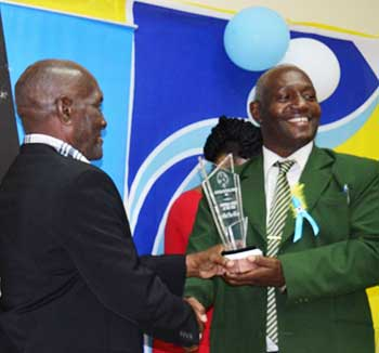 Image: (L-R) Albert 'Vasso ' receiving an award from SLFA 1st Vice President, Emmanuel Belase PHOTO: Anthony De Beauville)